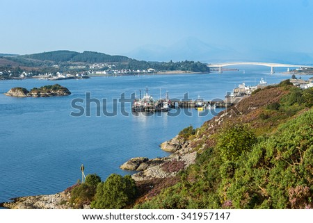 Skye from Kyle of Lochalsh, in the mainland Highlands of Scotland, in a sunny, bright day. Despite the boats and ferries docked at the loch harbor, the main link for transportation is the long bridge.