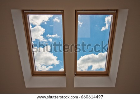 Skylights. View from the window. View of the sky from the window. Window on the roof. Sunlight through the attic window. Light in the house\n