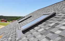 Skylights windows on modern house roof top.  Attic skylight windows on asphalt shingles roof.