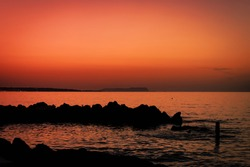 Skyline after sundown. Scenery of orange sky with rock silhouette and ocean waves. Orange sunset at shoreline photography. Waterfront tranquility in paradise on vacations. Majestic horizon wallpaper.