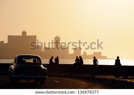 Skyline in La Habana, Cuba, at sunset, with vintage cars on the street and people sitting on the Malecon. Copy space