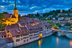 Skyline of Bern, capital of Switzerland at blue hour reflecting in Aare river. Panoramic view of old city, Nydegg Church and Untertorbrucke bridge. Landmark of historical town UNESCO World Heritage.