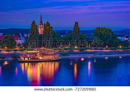 Skyline of Bonn, Germany. Beautiful night shot of great german city. Panorama with boat, trees, and historic architecture reflected in the water. #727209880