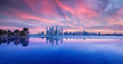 Skyline of Dubai Marina at a beautiful sunset with an infinity pool in front