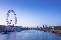 Skyline of London before sunrise with famous landmarks, Big Ben, Houses of Parliament, boat and clear blue sky - England, UK