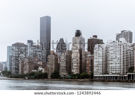 Skyline of Midtown of NYC from East River in Roosvelt Island a misty day #1243892446