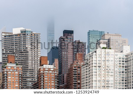 Skyline of Midtown of NYC from East River in Roosvelt Island a misty day #1253924749