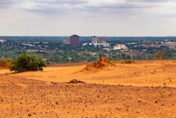 Skyline of Niamey capital of Niger seen from a higher sahelian dry plateau with a green bush and a termitary in foreground partially destroyed by the rains in the summer humid season