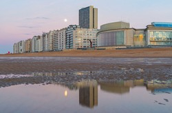 Skyline of Oostende (Ostend) with North Sea beach at sunset with full moon reflection, Belgium.