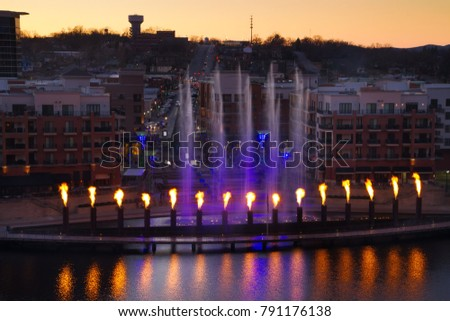 Skyline view of Branson, Missouri with the display showing at the landing waterfront park area.  The fountain has fire reflection into the water with tourist watching as they shop.