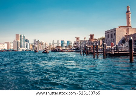 Skyline view of Dubai Creek with traditional boats and piers. Sunny summer day. Famous tourist destination in UAE. Creative color post processing.