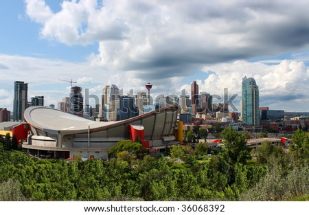 Skyline view of highrise office and apartment buildings in Calgary, Alberta, Canada with the Saddledome in the foreground and dramatic sky