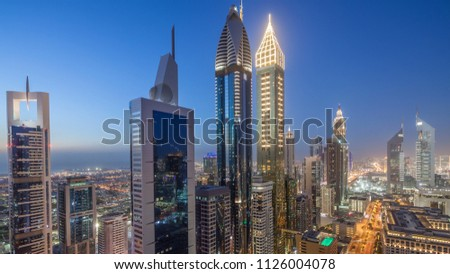 Skyline view of the buildings of Sheikh Zayed Road and DIFC day to night transition timelapse in Dubai, UAE. Skyscrapers in financial centre aerial view from above after sunset #1126004078