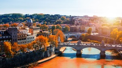 Skyline with bridge Ponte Vittorio Emanuele II and classic architecture in Rome, Vatican City scenery over Tiber river. Autumn view with red foliage.