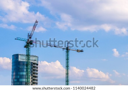 Skyscraper under construction. Crane near skyscrapers. Construction site with crane and building.