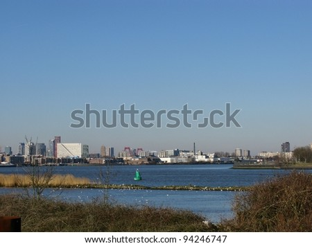Skyscrapers along the river meusse in Rotterdam seen from the nature island Brienenoord in the Netherlands