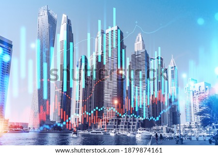Skyscrapers of Dubai business downtown. International hub of trading and financial services of Western Asia. FOREX graph and chart concept. Double exposure. Dubai Canal waterfront.