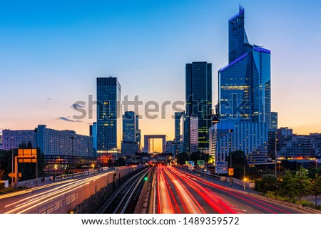 Skyscrapers of La Defense modern business and financial district in Paris. Long exposure of multi-lane road with skyscrapers of business district La Defense, Paris, France