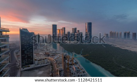Skyscrapers on Al Reem in Abu Dhabi timelapse during sunrise from above. Aerial citiscape from Al Reem Island at morning with fog. Sun reflected on glass surface