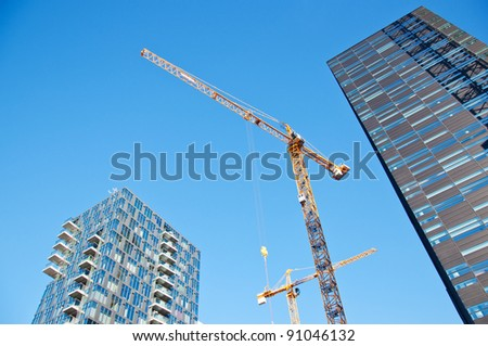 Skyscrapers with tower cranes on sky background