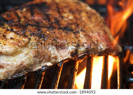 slab of ribs on grill with flames