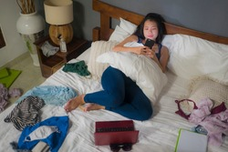 slackness and disorganized during covid-19 home lockdown - young disorderly and chaotic Asian Chinese woman on bed using internet mobile phone on grimy messy bedroom in social media addiction