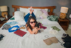 slackness and disorganized during covid-19 home lockdown - young disorderly and chaotic Asian woman on bed using internet mobile phone on grimy messy bedroom in social media addiction