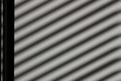Slanted black stripes on the gray wall. Multi-tone textures from different textures of different grayscale. Textures. Copy space.