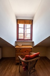 Slanted cathedral ceiling and window in loft vertical view with table and chair in dark bedroom home apartment room in Europe