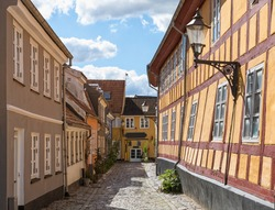 Slanted houses on cobblestone street at the old town of Aalborg, Denmark