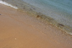 Slanted perspective of beach and shorline sand and water close up
