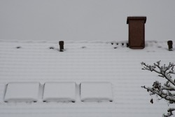 Slanted roof with a chimney and three skylights covered in a layer of thick, fresh snow