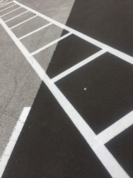slanted white crosswalk on black ground leading to gray