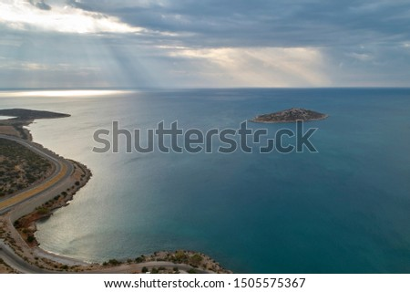 Slanting sunbeams break through the clouds to the surface of the sea. Island in the sea and winding road in the morning. Aerial view #1505575367