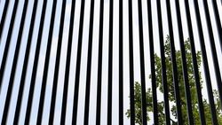 Slat shading light. Black silhouettes of metal lattice fences adorn vertical modern houses or buildings with green plant background and blue sky. Selective focus