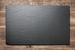 Slate blackboard on wooden background