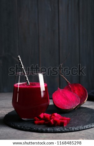 Slate plate with glass of beet smoothie on table, space for text