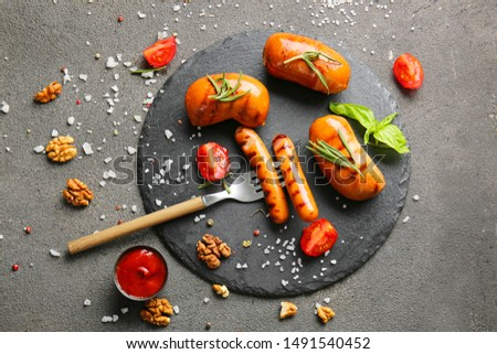 Slate plate with tasty grilled sausages and sauce on grey background Stock photo ©