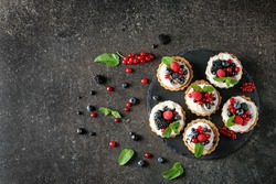 Slate plate with tasty tartlets and berries on table, top view