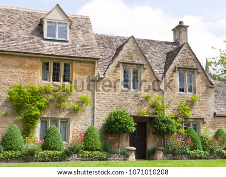 Slate roof golden stone cottage with topiary plants, colorful flowers in front, rural village in Cotswolds, UK . #1071010208