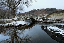 Slaters Bridge in Little Langdale on a cold Winters morning with snow on rocks. Lake District, UK.