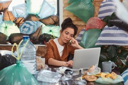 Slatternly Asian woman sitting before laptop and holding smartphone close to ear among leftovers, plastic bags and rubbish on background