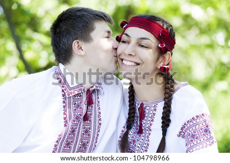 Slav girl and young cossack kissing at nature.