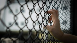 Slavery trade and trafficking victim concept of woman prisoner in jail being tortured, punished or abused in violation with hand holding cage wire mesh