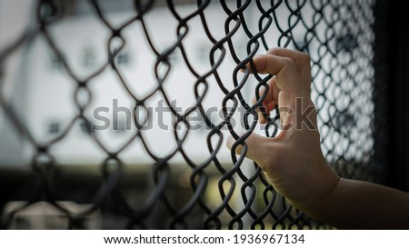 Slavery trade and trafficking victim concept of woman prisoner in jail being tortured, punished or abused in violation with hand holding cage wire mesh Сток-фото ©