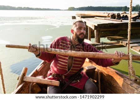 Slavic warrior in the clothes of the Viking Age sailed from the pier in a boat. reconstruction of life and ships of 9-11 centuries, a festival of historical reconstruction.
