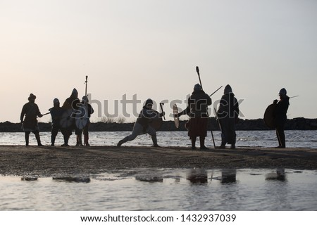 Slavic warriors reenactors with wearpons and shields training fighting outdoors at seaside