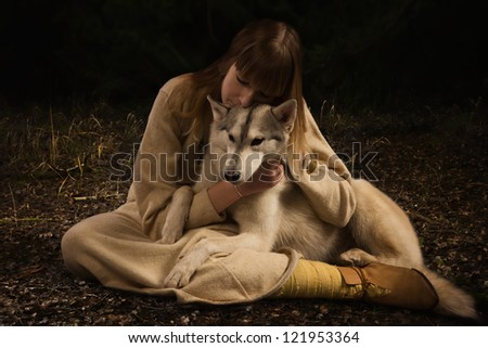 Slavonian girl in the traditional suit and siberian husky in the deep forest - stock photo