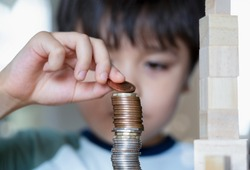 Slective focus Kid stacking sterling pound coin and pennies nickels on wooden table, Blurry face Child boy looking at money coins, Learning financial responsibility and saving future