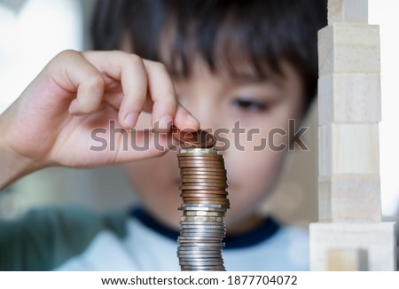 Slective focus Kid stacking sterling pound coin and pennies nickels on wooden table, Blurry face Child boy looking at money coins, Learning financial responsibility and saving future Zdjęcia stock ©